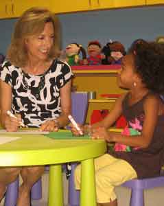 Child Advocates volunteer coloring with child